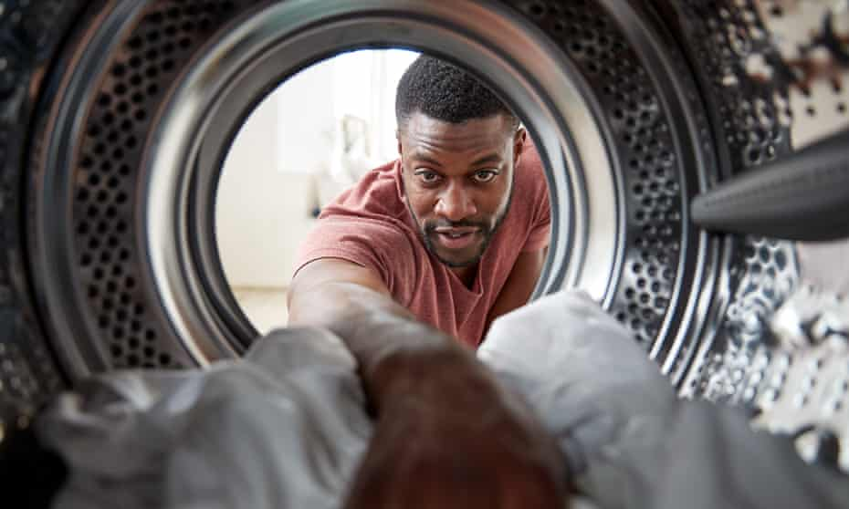 Posed by model View Looking Out From Inside Washing Machine As Man Does Laundry