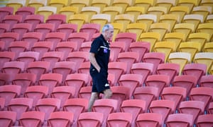 Rabbitohs coach Wayne Bennett is seen walking amongst the empty grandstand seats on full-time after losing the round two NRL match to the Brisbane Broncos.
