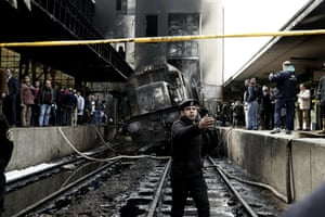 A policeman stands guard after a train rammed into a barrier at Ramsis station in Cairo, 27 February