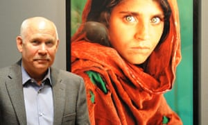 Steve McCurry poses in front of his photo Afghan Girl.
