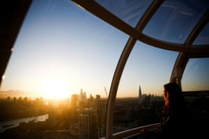 A woman watches the sunrise from a pod at the top of the London Eye