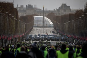 Protesters walk towards a police line on the Champs Elysées during the 'yellow vests' demonstration