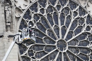 A firefighter stands in an aerial lift in front of a stained-glass window