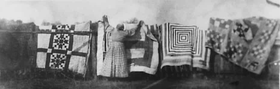 Damp river air … a woman drying quilts circa 1900.