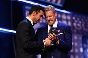 Peter Schmeichel hands over the best goalkeeper award to Gianluigi Buffon.