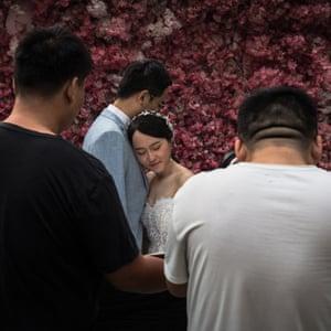 A couple pose for a photographer taking their pre-wedding photos at 27 Rome Brand photo studio