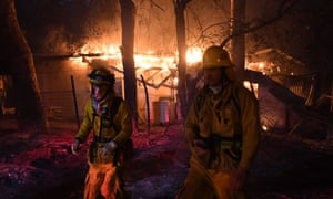Firefighters move away from a burning house after discovering downed live power lines, as the Thomas wildfire continues to burn in Carpinteria.