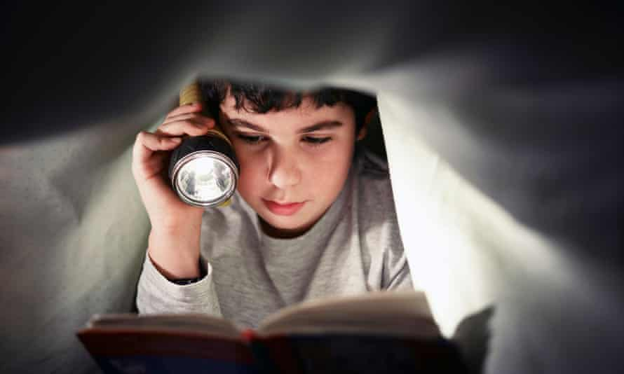 A boy reading a book under the bed covers.