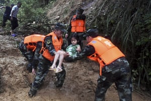 Rescuers lift a girl to safety after heavy rain and flooding in China