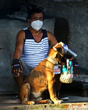 A dog using a face mask with quarantine pass and carrying a sanitation kit with his master along Sumulong Highway in Antipolo City, Philippines, on 18 Sep 2020.