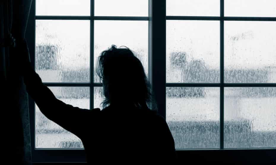 A woman looking out of a window on a rainy day