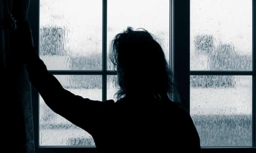 Woman looking out of window on rainy day