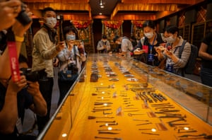 Journalists and officials look at a display of traditional Tibetan medicine during a government organized visit for journalists to the Ganlu Tibetan Medicine Co.