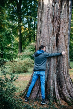 A visitor hugs a Giant Redwood at Westonbirt