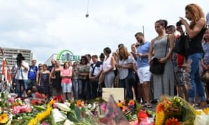 People stand next to flowers laid for the victims of the shooting