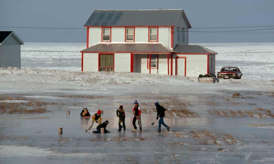 Children play ice hockey along shoreline of Saint Lawrence River.