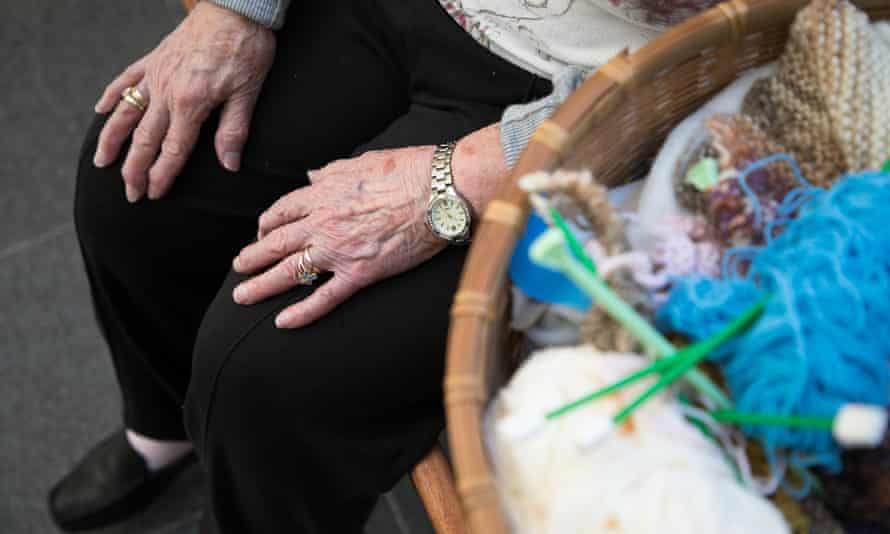hands of an older woman on her knees and a basket of wool and knitting needles