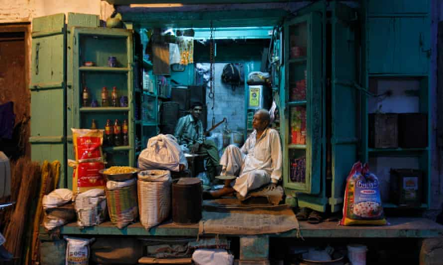 A shopkeeper and his sales assistant wait for customers inside a family-owned grocery store in an alley in the old quarters of Delhi.
