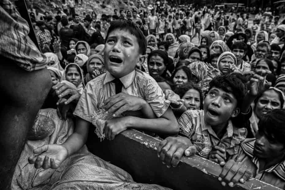 A Rohingya boy cries as he clambe on to a truck distributing aid for a local NGO, near the Balukali refugee camp in Cox's Bazar, Bangladesh