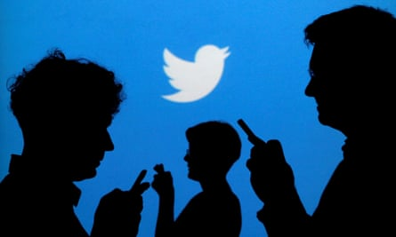 Silhouette of people using phones in front of Twitter  backdrop