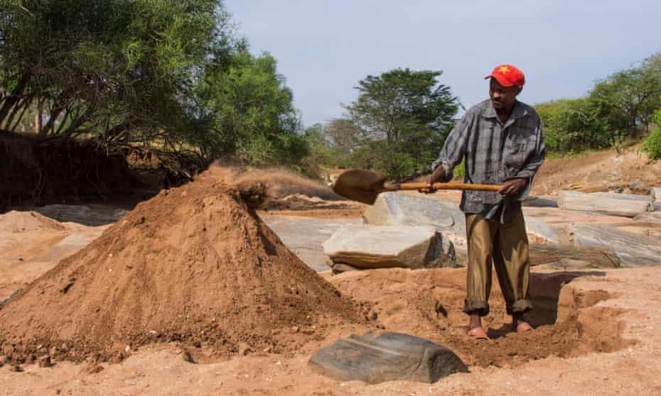 A man harvests sand in Makueni, Kenya.