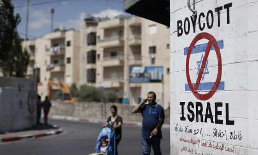 Palestinians walk past a sign painted on a wall in the West Bank town of Bethlehem calling for a boycott of Israeli products from Jewish settlements. The international BDS (boycott, divestment and sanctions) campaign aims to exert political and economic pressure over Israel's occupation of the Palestinian territories.