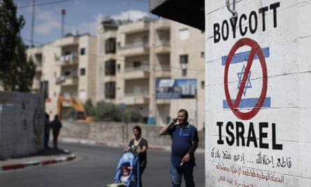 Palestinians walk past a boycott sign in Bethlehem. UK councils are to be told they cannot conduct their own foreign policy campaigns through their procurement and investment policies.