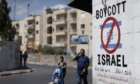 Palestinians walk past a sign painted on a wall in the West Bank town of Bethlehem.