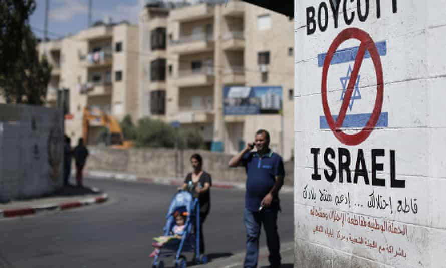 Palestinians walk past a sign painted on a wall in Bethlehem last year calling for a boycott of Israeli product