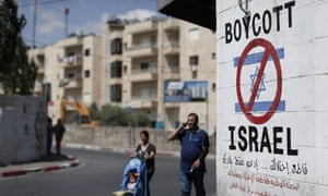 Palestinians walk past a sign on a wall in Bethlehem