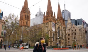 A woman walks past St Paul's Cathedral while wearing a face mask as a preventive measure against the spread of novel coronavirus Covid-19 in Melbourne