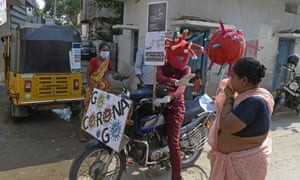 An employee of a private hospital wearing headgear themed on Covid-19 coronavirus rides his motorbike around counselling people at markets and slums about the precautionary measures to be taken against the spread of the coronavirus in Hyderabad on May 31, 2021. (Photo by Noah SEELAM / AFP) (Photo by NOAH SEELAM/AFP via Getty Images)