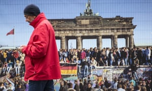 A man passes a poster from the fall of the Berlin Wall, near the Brandenburg Gate, Berlin, on German Unity Day, 3 October 2017
