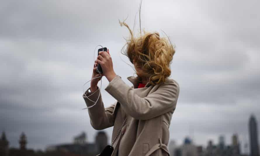A tourist takes a photograph during strong winds on Westminster Bridge in London