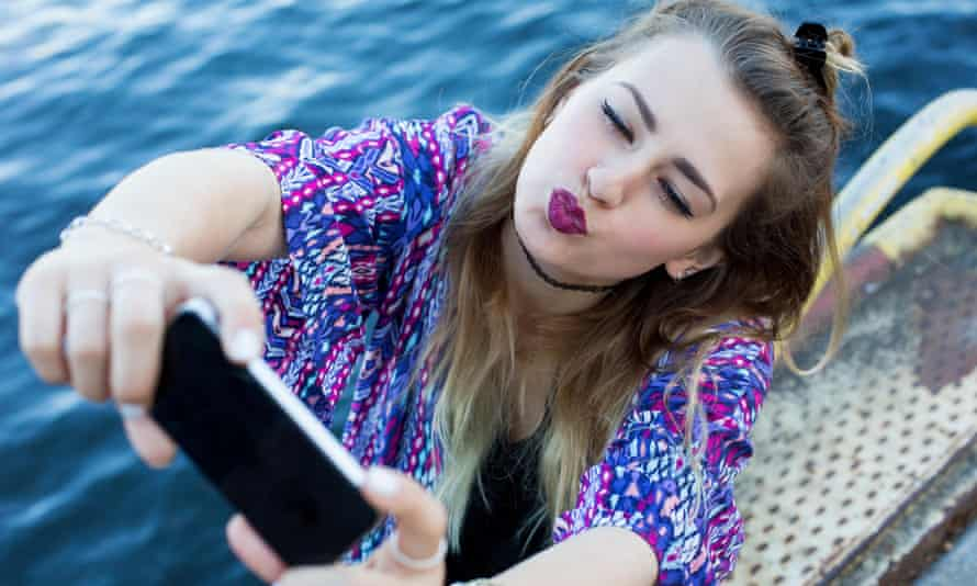 young woman by the waterfront taking a selfie