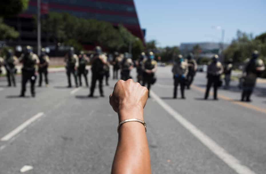A participant raises a fist against police officers during a Black Lives Matter march in Los Angeles on 14 June 2020.