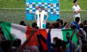 Harry Kane speaks to the media infront of celebrating Italian fans.