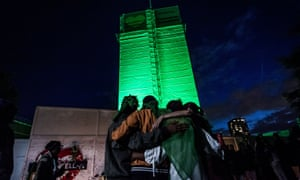 People embrace each other at the foot of Grenfell Tower in west London on the first anniversary of the fire that killed 72 people.