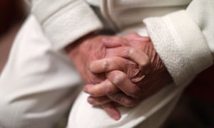 An older woman clasps her hands together