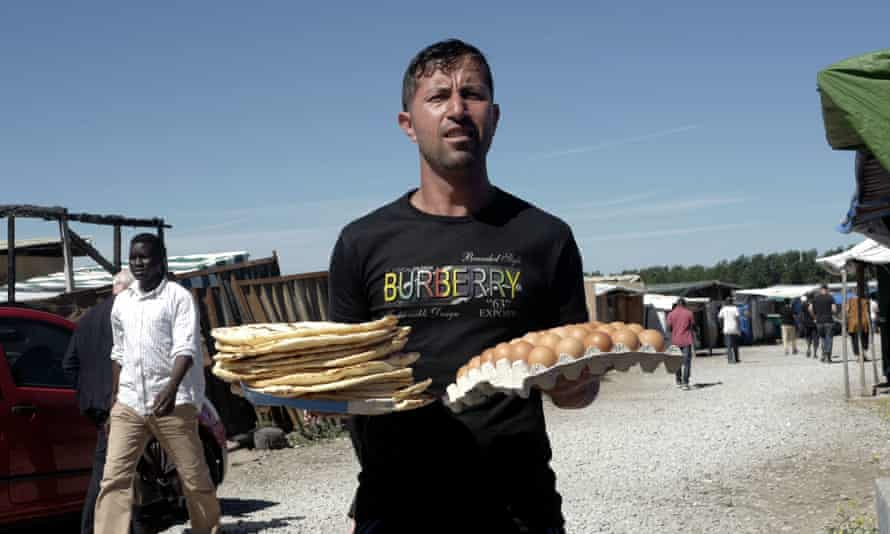 An Afghan migrant walks with food at the migrant camp in Calais, northern France