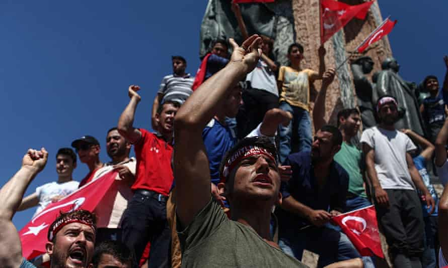 People wave Turkish flags in Taksim Square, Istanbul.