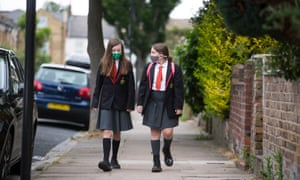 Two girls in face masks walk to school