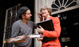 A stylist making the finishing touches to a newly unveiled wax figure of Theresa May.
