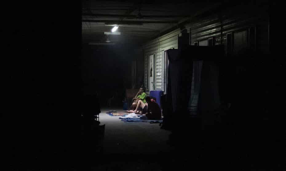 Refugees sit under a battery-powered light.