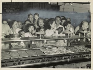 A hungry crowd waits for hot dogs cooking on the grill in 1947