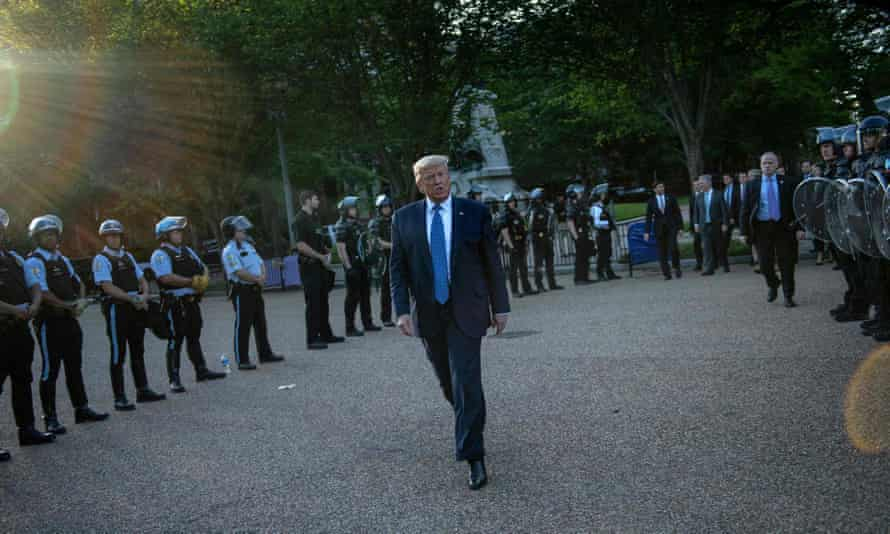 Trump is flanked by police as he walks from the White House to nearby St John's Episcopal church on Monday.