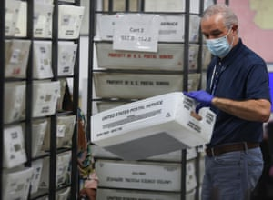 A worker of Miami-Dade County Elections Department holds a U.S. Postal Service basket with mail-in ballots during the primary election amid the coronavirus outbreak in Miami, Florida.