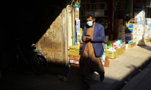A man wearing a protective facemask walks in Herat city on 24 February