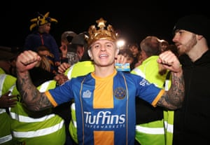 Shrewsbury Town's Jason Cummings celebrates at full time as fans invade the pitch following the 2-2 draw.