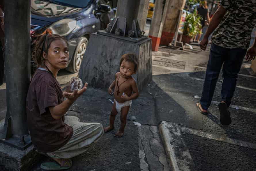 A homeless woman in Malate seeks change to buy food for her toddler. The streets of Manila are home to thousands of homeless Filipinos who sleep on the sidewalks, sea walls, under awnings and in stairwells - anywhere they can get rest without being told to move on